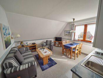 Wohnzimmer mit Sitzecke, Esstisch und Küchenzeile